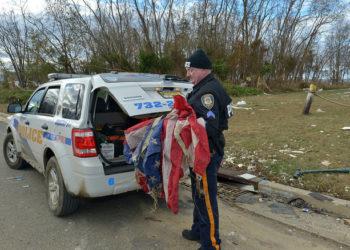 Nowojorski policjant sprząta flagi narodowe po uderzeniu Huraganu Sandy (fot. Flicker-Creative Commons)