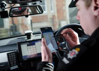 Angielski policjant z urządzeniem przenośnym